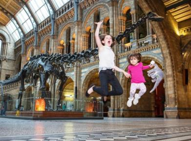 2 children jumping in front of Dippy.