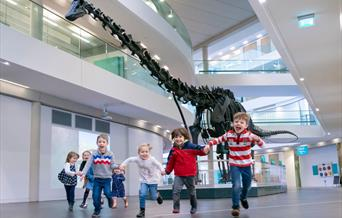 Children running towards the camera with Dippy behind them.