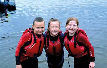 3 children at the water's edge, wearing lifejackets.