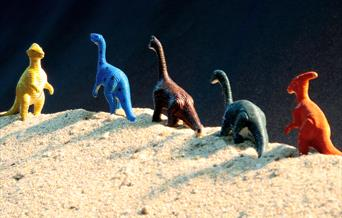 A line of toy dinosaurs in the sand.