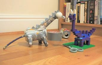 2 model dinosaurs made of junk and Lego.