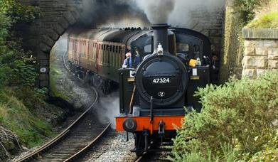 A steam train billowing smoke as it clears a tunnel.