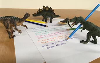 Dinosaur models standing on a written short story.